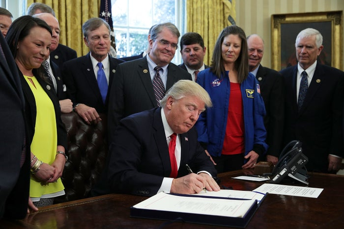 Rep. Martha Roby and other members of Congress watch as President Donald Trump signs the National Aeronautics and Space Administration Transition Authorization Act of 2017.