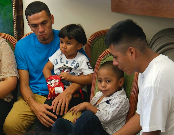 Javier Garrido Martinez (left) and Alan Garcia (right) sit with their 4-year-old sons at a news conference July 11. The men were reunited with their children after almost two months of separation.