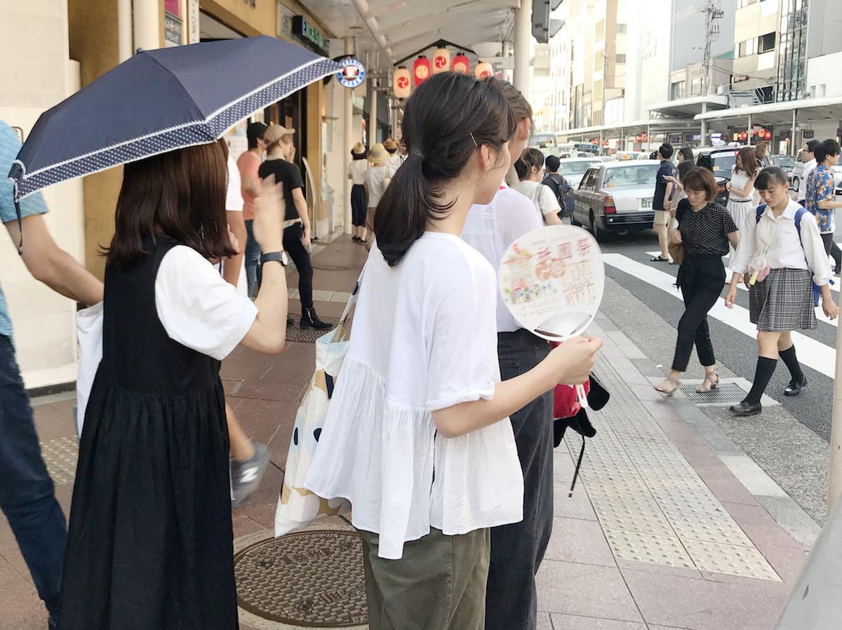 うちわで顔をあおぎながら街を歩く女性ら(19日、京都市内)