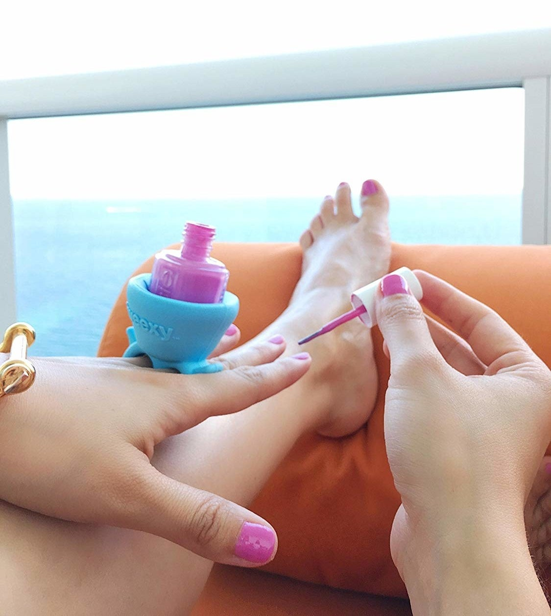 model paints nails while wearing a ring with nail polish bottle in it