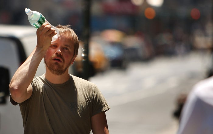 A man tries to cool himself with a bottle of water during the first heat wave of the year on June 9, 2008, in New York City.