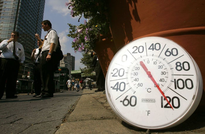 A thermometer on the sidewalk indicates a temperature of 120 degrees as people eat ice cream in New York City's Upper West Side on Aug. 2, 2006.