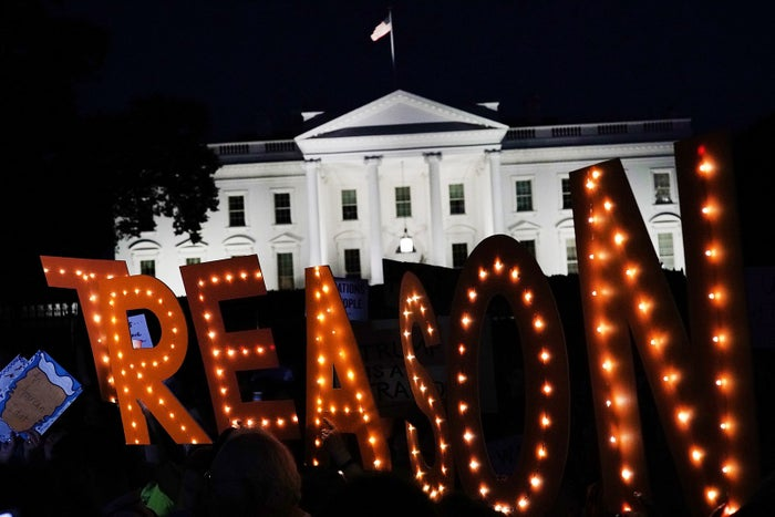 """Activists participating in a vigil hold up a sign that reads """"Treason"""" in front of the White House on July 18 in Washington, DC."""