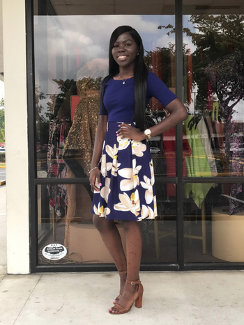 reviewer wears midi dress with quarter sleeves that's solid color on top and printed on the skirt