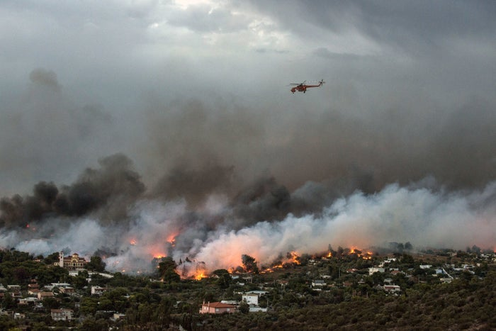 A firefighting helicopter flies over a wildfire raging in the town of Rafina near Athens Monday.