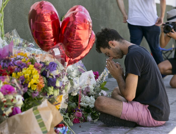 Paolo Singer prays at a makeshift memorial on the sidewalk outside the Trader Joe's store.
