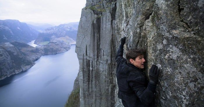 Tom Cruise hanging off a cliff, as usual, in Mission: Impossible — Fallout.