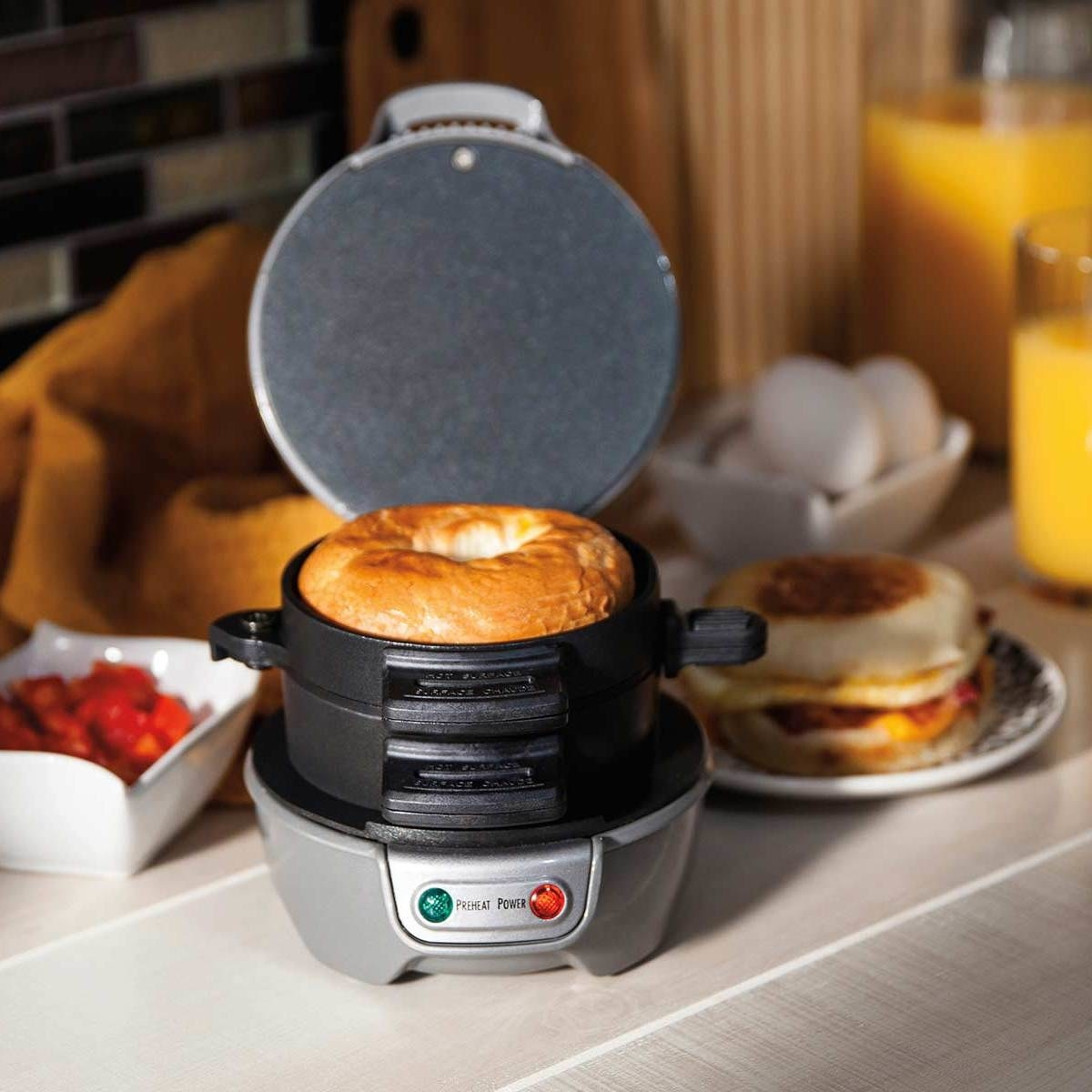 The silver sandwich maker with a bagel slice loaded on the top cooking plate