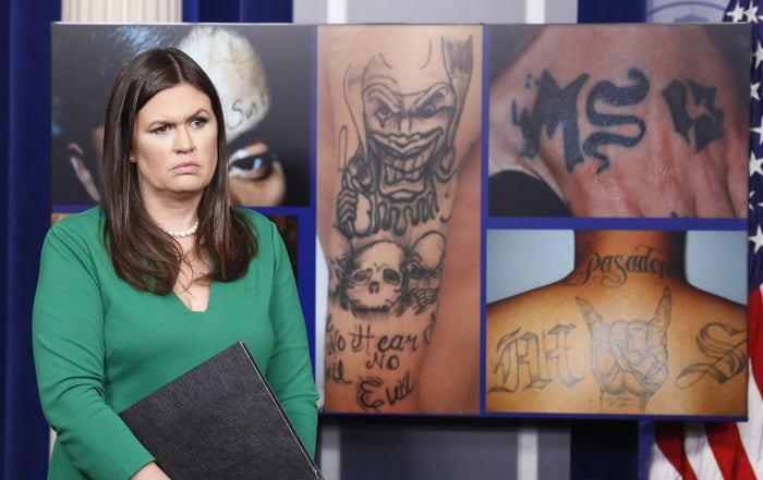 White House press secretary Sarah Huckabee Sanders stands in front of pictures of MS-13 gang tattoos during a press briefing at the White House.