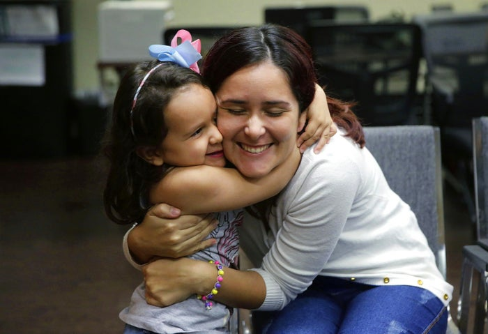 Natalia Oliveira da Silva and her daughter, Sara, 5, hug as they wait at a Catholic Charities facility on July 23, in San Antonio. Since their separation in late May, the girl had been at a shelter for immigrant children in Chicago, while Oliveira was taken to various facilities across Texas.