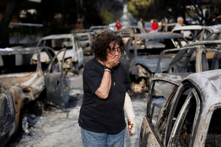 A woman tries to find her dog following a wildfire at the village of Mati, near Athens.