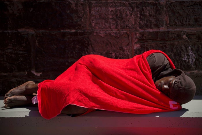 A man wrapped in a Red Cross blanket sleeps after arriving aboard a coast guard boat at the harbor in Tarifa, Spain, on July 24, after an inflatable boat carrying 135 migrants was rescued by the Spanish coast guard in the Mediterranean.