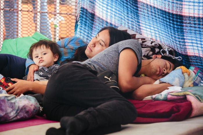 Carlos and Karina, 20, of Puebla, and their son, Leo Alexander, 11 months, await their chance to speak to Border Patrol officers on June 23 at the border crossing between Nogales, Sonora, and Nogales, Arizona.