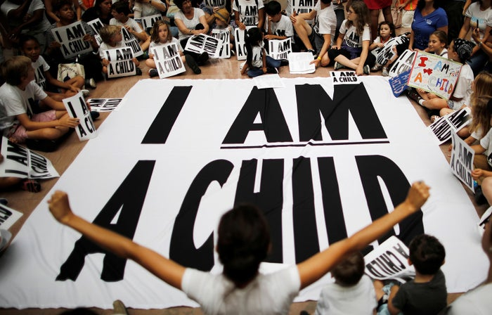 Children and family members take part in a sit-in in Washington, DC, following a march to mark the court-ordered deadline for the Trump administration to reunify thousands of families separated at the border on July 26.