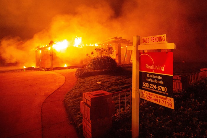 A real estate sign is seen in front of a burning home in Redding.