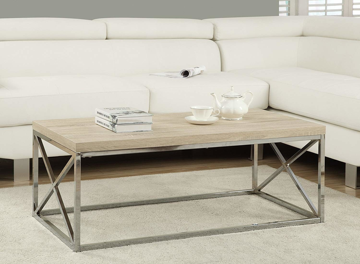 The coffee table with a light brown wood top and silver legs