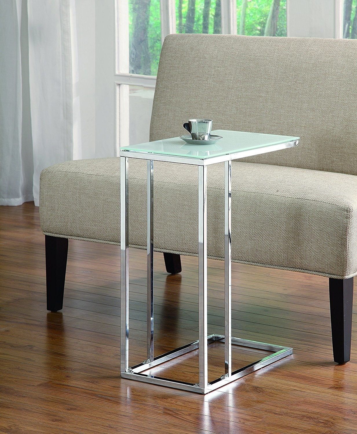 The table with a glass top and silver legs