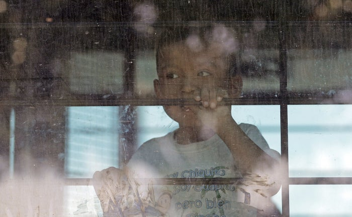 An immigrant child looks out from a US Border Patrol bus outside a processing center in McAllen, Texas, June 23.