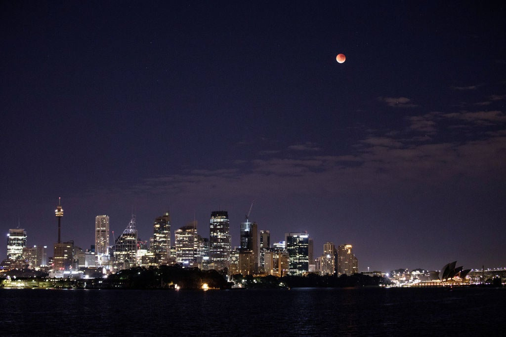 The moon turns red over the Sydney skyline in Australia.