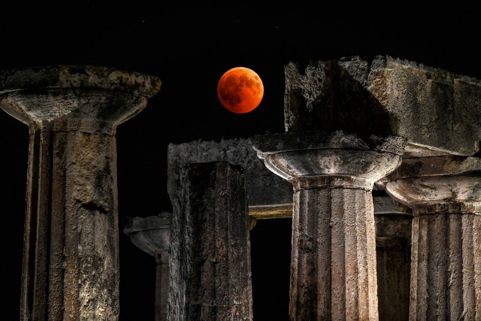 The moon rises over the temple of Apollo in Corinth, Greece.