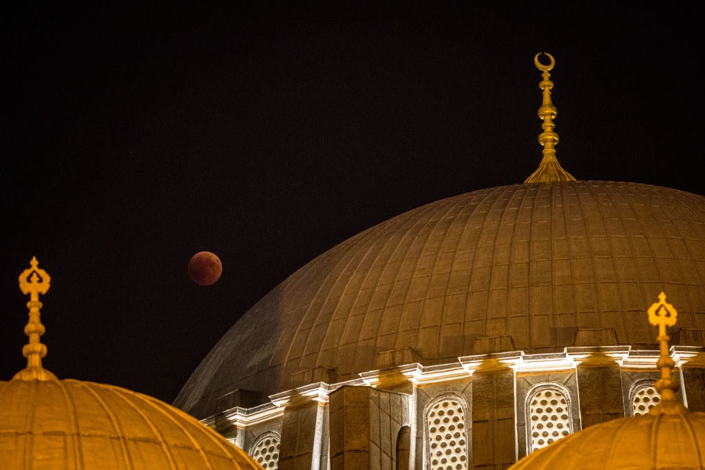 A blood moon is seen behind a dome of the Suleymaniye Mosque in Istanbul, Turkey.