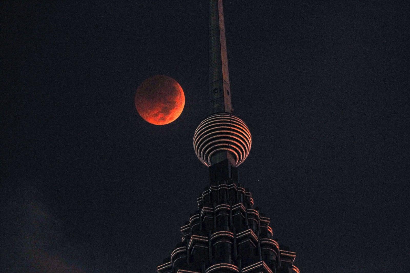 The blood moon is seen above Petronas Twin Tower in Kuala Lumpur, Malaysia.