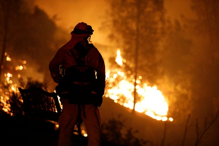 A firefighter watches flames advance up a hill toward homes as crews battle the Carr Fire, west of Redding.