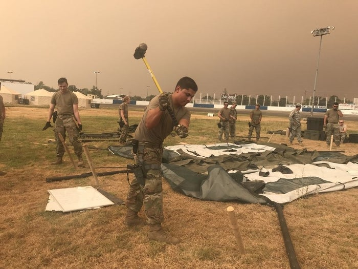 Members of the California National Guard put up a tent at the Shasta District Fairgrounds shortly after arriving in Anderson, California, to support firefighting operations for the Carr fire.
