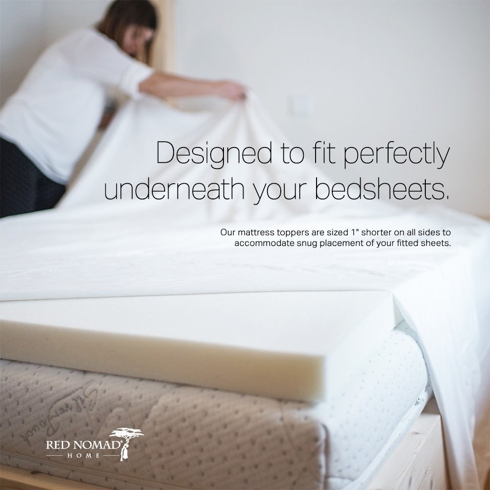 The topper on a mattress with model putting sheets over it