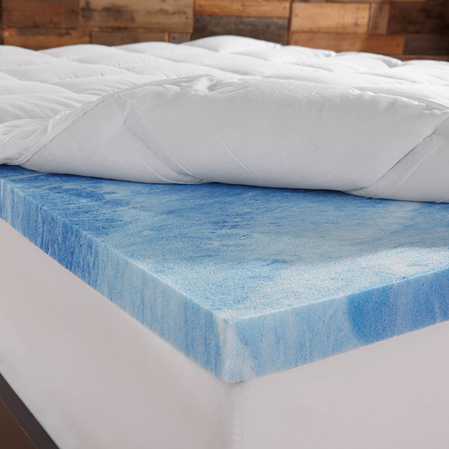 A bed with the topper; the fiber-fill layer pulled back to show the memory foam pad