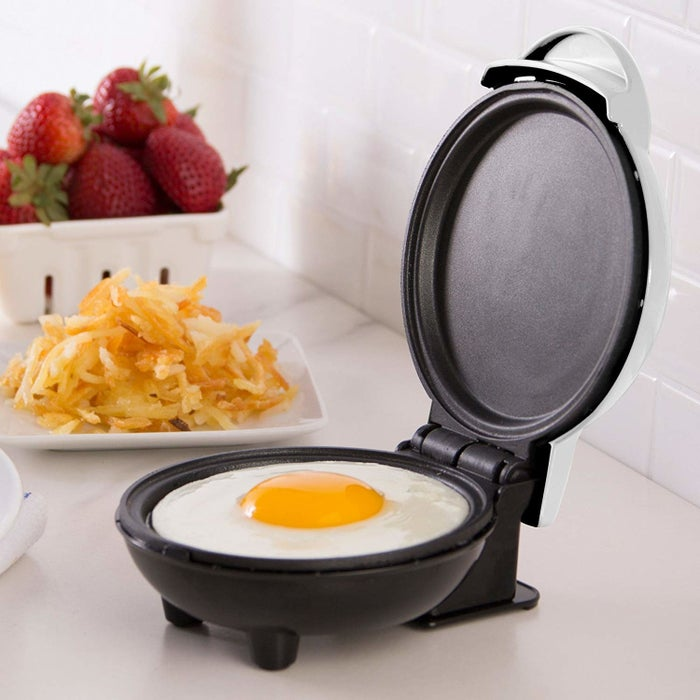 "Promising review: ""I LOVE this little gem. The portion size is perfect for one (me). Just be creative...it cooks stir-fry-size meats quickly and perfectly. It makes a grilled cheese on a small bun and a perfect egg. Clean up is so easy and quick. I love not messing up a pan and the stove. I like to eat, but for me, cooking for one is not especially fun. This is almost fun and so easy. All I really use now is my Dash, microwave, and coffee pot. Kitchen stays immaculate!"" —JaiyenPrice: $14.99+ or as an add-on item for $9.99 (available in seven colors)"