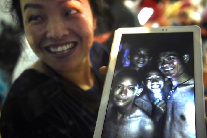 A family member shows a picture of four of the 12 missing boys near the Tham Luang cave.