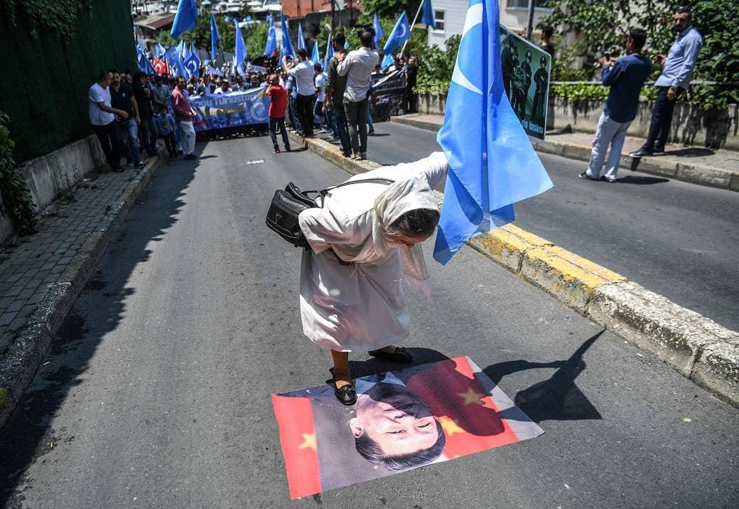 東トルキスタン(ウイグル人の分離主義者が「新疆」に対して用いる名称)の旗を手に持ち、中国の習近平国家主席のポスターに唾を吐きかける女性。7月5日、イスタンブールにある中国領事館の前で行われた抗議運動での一幕。