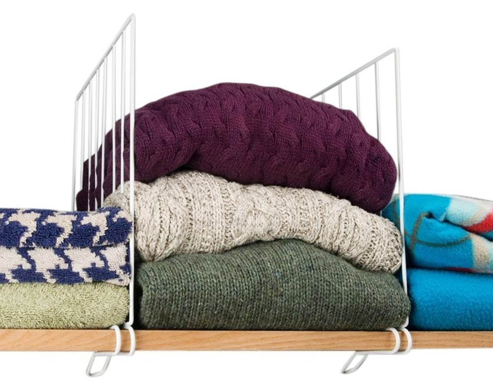 wooden shelf with white wire shelf dividers in between vertical stacks of sweaters and blankets