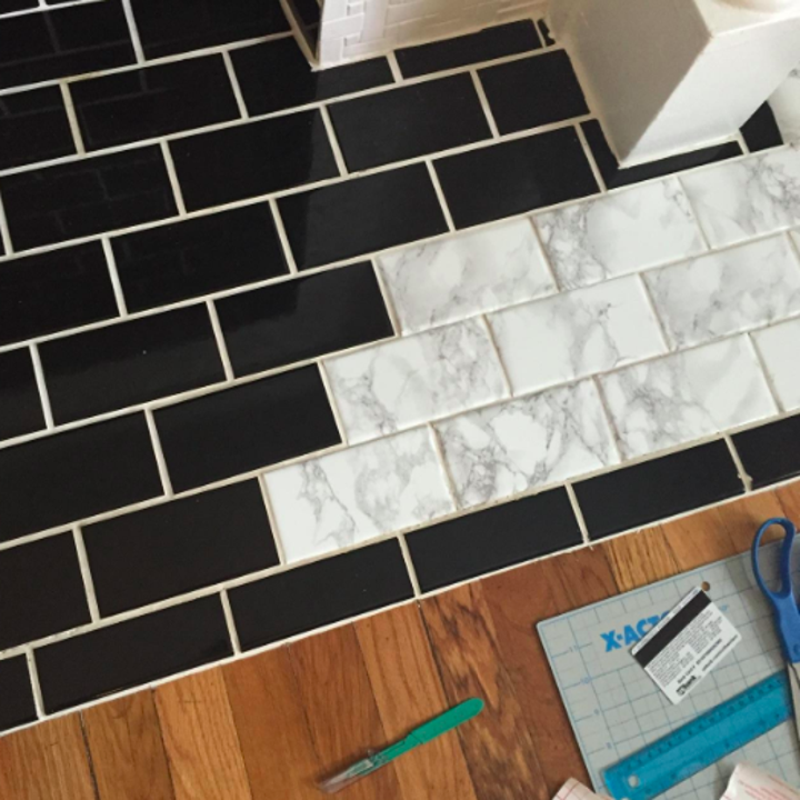 black tiles with some covered in the marble contact paper