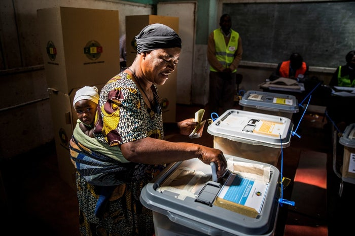A woman carrying her baby casts her ballot at a polling station in the suburbs of Mbare, located in Harare.
