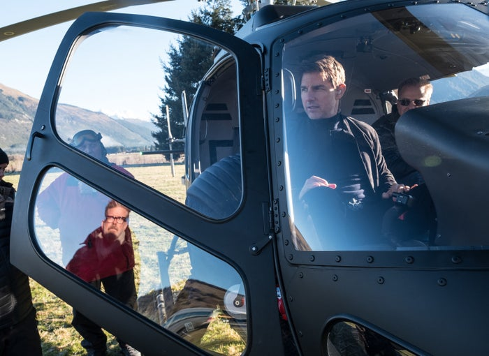 Director Christopher McQuarrie (reflected in window) and Cruise on the set of Mission: Impossible — Fallout.
