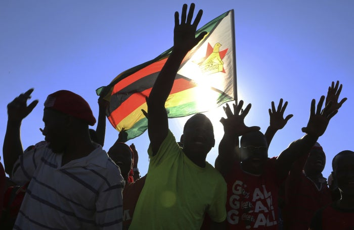 Supporters carry the Zimbabwean flag at a Nelson Chamisa, head of the MDC opposition alliance, rally in Chitungwiza.