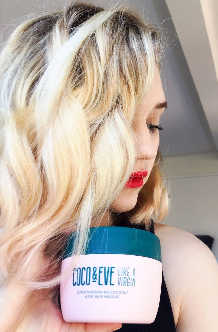 A person with wavy and shiny hair holding a hair mask container