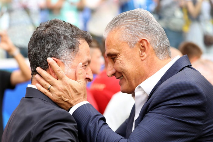 Brazilian coach Tite holds his Mexican counterpart Carlos Osório's face, before the quarter-finals match between the two teams.