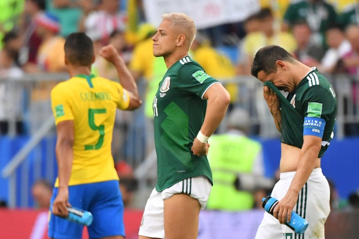 Hernandez and Guardado of Mexico grieve their team's elimination. In the background, Brazilian forward Casemiro celebrates.