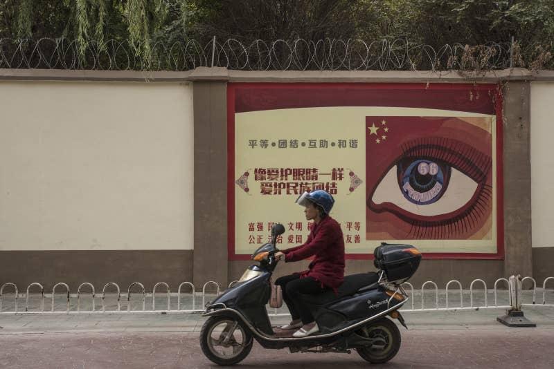 再教育施設の前をバイクで通り過ぎる女性。その塀には、プロパガンダ用ポスターが貼られている。2017年10月、カシュガル市で撮影。