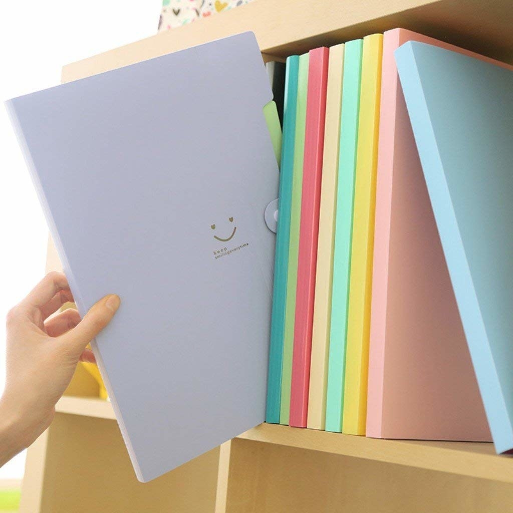A hand pulling the lavender folder with a small smiley on front from a shelf full of the pastel folders