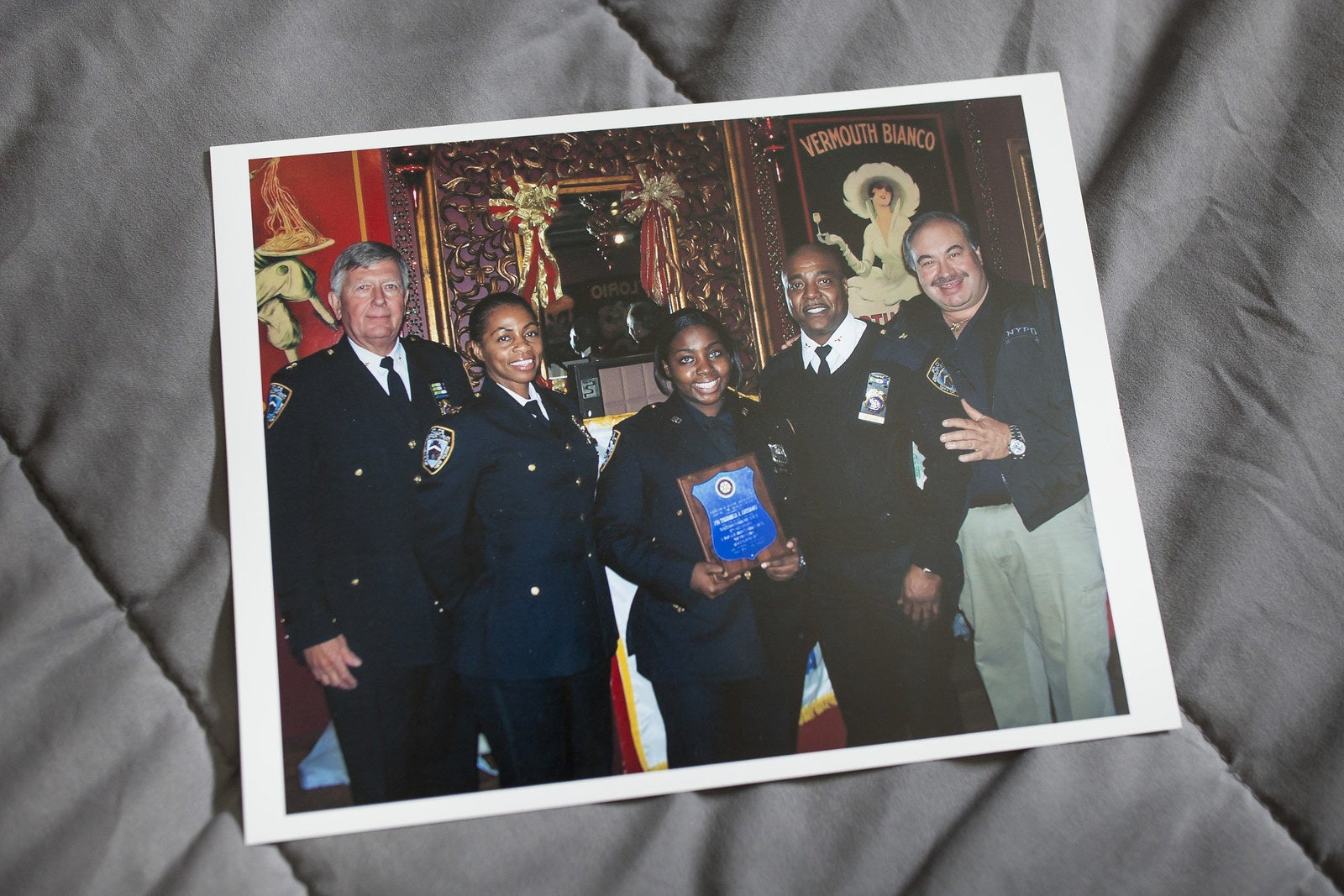 Inserillo (center) holds a plaque when she won officer of the month.