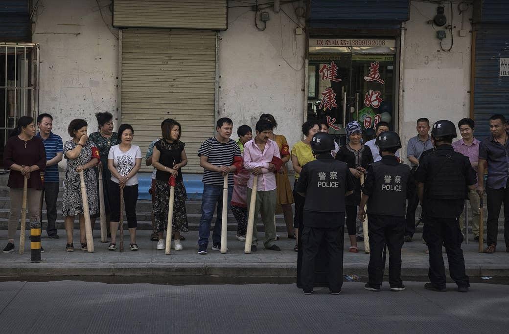 こん棒を手に持って安全対策の訓練を受ける、ウイグル人と漢人の店主たち。新疆ウイグル自治区の南西部にある古い街、カシュガル市の近郊で、2017年6月27日撮影。