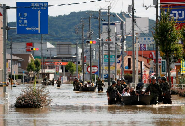 Japan Self-Defense Forces soldiers rescue people from a flooded area in Mabi town in Kurashiki, Okayama prefecture.