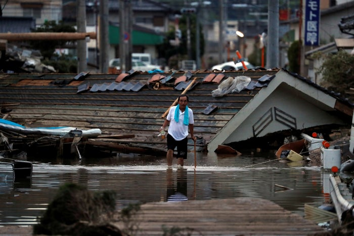 A resident walks in front of submerged and destroyed houses in a flooded area in Mabi town in Kurashiki, Okayama prefecture.