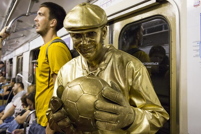 A man on the Moscow subways is painted entirely in gold as he celebrates a victory by the Russia team over Spain on July 1.