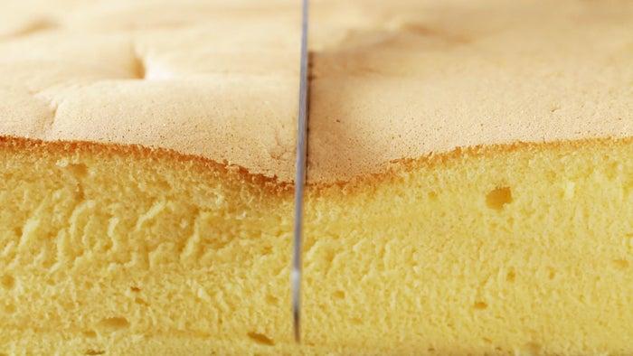 24×24×6cm角型 1台分材料:グラニュー糖 140g薄力粉 130gサラダ油 80ml牛乳 80ml卵 8個作り方1. オーブンは170℃に予熱しておく。2. 小鍋にサラダ油を入れ、小さな気泡が出るまで中火で30秒ほど温める。3. サラダ油をボウルに移し、薄力粉をふるい入れて泡立て器で混ぜたら、牛乳を2回に加えてよく混ぜる。4. 卵黄が入ったボウルに(3)を加えて、なめらかになるまでよく混ぜる。5. ボウルに卵白を入れ、白っぽくなるまでハンドミキサーで泡立てる。グラニュー糖を3回に分けて加え、そのつどよく混ぜる。6. ツノが立つくらいまでしっかり泡立てたら、(4)のボウルに1/4量を加えて、気泡をつぶさないようにしてゴムベラで混ぜ合わせる。残りのメレンゲも2回に分けて加え、そのつどよく混ぜる。7. 紙を敷いた型に(6)を流し入れ、少し高い位置から2、3回落として気泡を抜く。8. 天板にタオルをしいて(7)を置き、熱湯を注いだら、170℃に予熱したオーブンで60分湯煎焼きする。9. 焼きあがったら型の底を叩いて蒸気を抜き、そっと型から外して、紙も外す。10. 好みの大きさに切り分けて皿に盛ったら、完成!