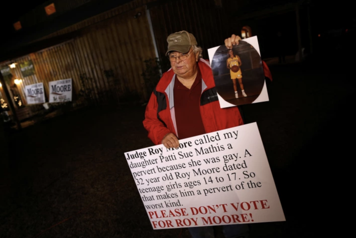 Nathan Mathis holds up a photo of his daughter, Patti Sue, before a campaign rally for Roy Moore in Alabama, on Dec. 11, 2017.